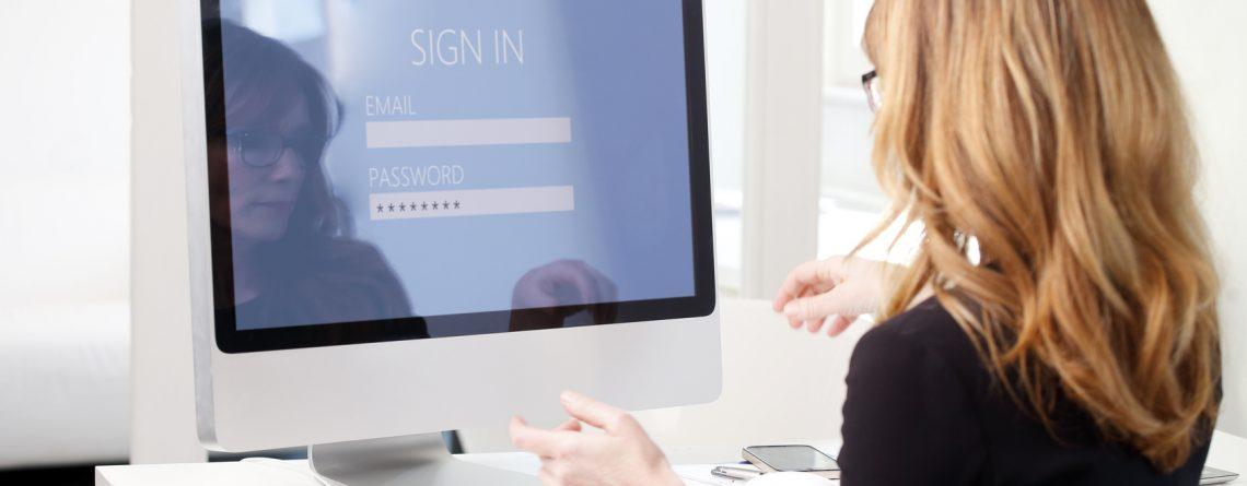 Eine Dame meldet sich mit einem Passwort an einem Rechner an.