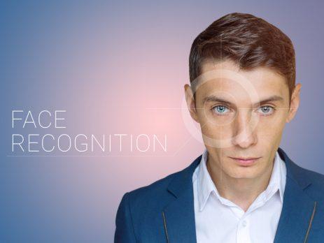 """Es ist ein Mann zu, sehen dessen Auge durch eine transparenten Zielscheibe fokussiert wird. Daneben ist der Schriftzug """"Face Recognition"""" geschrieben."""