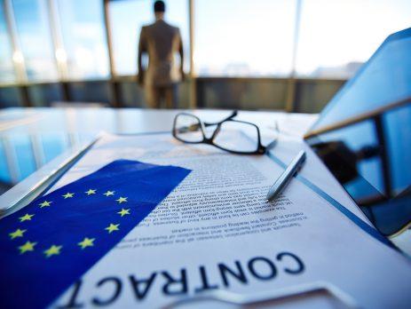 Es ist ein Schreibtisch zu sehen auf dem eine Brille, ein Kugelschreiber, eine EU-Flagge, ein Vertrag und ein Tablett liegen. Dahinter erkennt man in Unschärfe, einen zum Fenster hinausblickenden Herren.