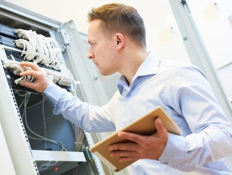 Ein Mann mit einem Tablet in einer Hand, hantiert mit der anderen Hand an einem Server herum