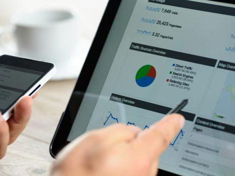 Es sind ein aufgestelltes Tablet und ein Smartphone zu erkennen auf denen Statistiken, ähnlich denen von Google Analytics, zu erkennen sind. Eine Hand deutet mit einem Stift auf ein Schaubild des Tablets.