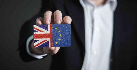 Datenschutz im Brexit. Ein Mann im Anzug hält einen Gegenstand nach vorne auf dem die UK- und EU-Flaggen abgebildet sind.
